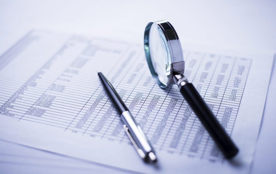conceptual image analysis of financial statements, documents, dollars, magnifying glass and pen on office desk